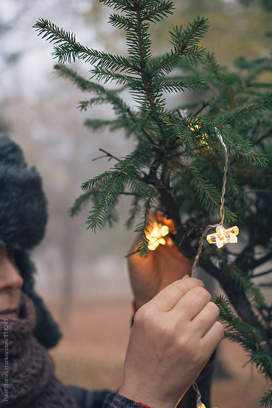 Woman decorating Christmas tree by Pixel Stories for Stocksy United