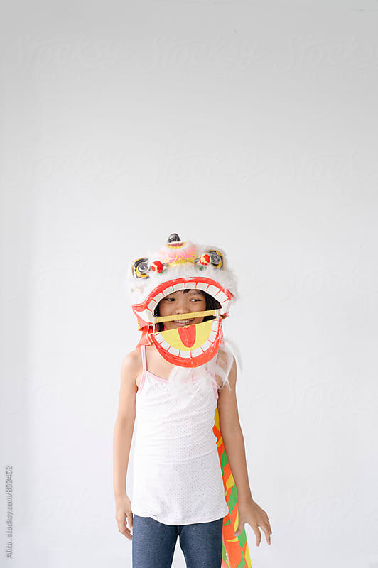 Little girl wearing Chinese lion dance head by Alita Ong for Stocksy United