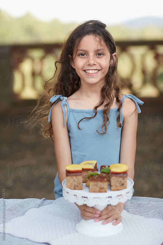 Smiling young girl with a plate full of cakes by Miquel Llonch for Stocksy United