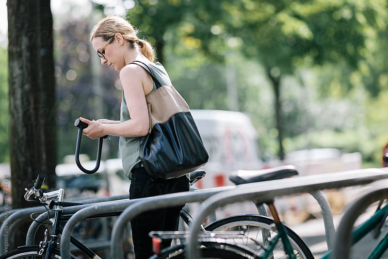Female Office worker locking Bicycle to rack by VegterFoto for Stocksy United