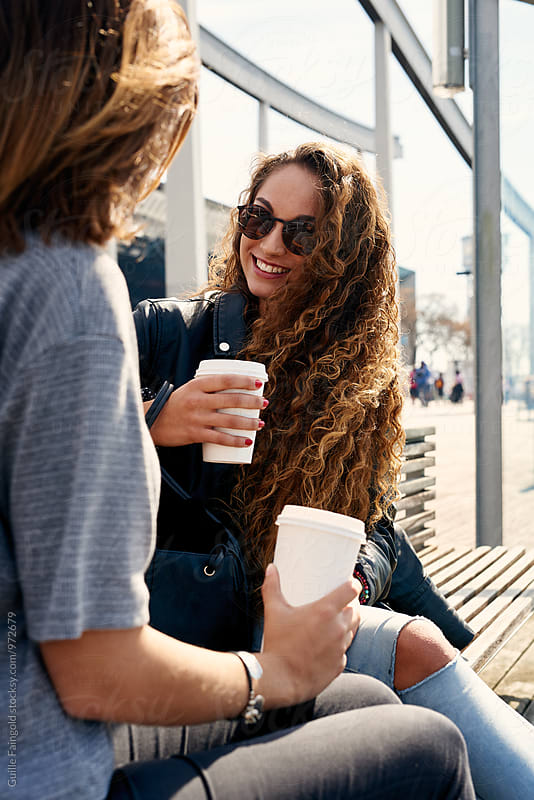 Two friends with coffee outdoors. Barcelona by Guille Faingold for Stocksy United