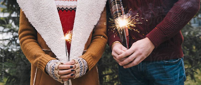 Couple holding Christmas sparklers. by Danil Nevsky for Stocksy United