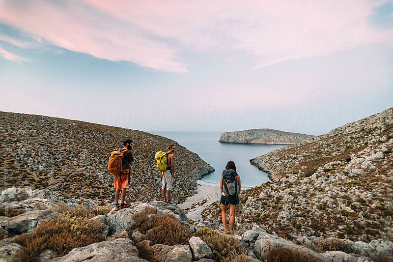 A group of hikers enjoying a sunset view over a scenic greek cove by Micky Wiswedel for Stocksy United