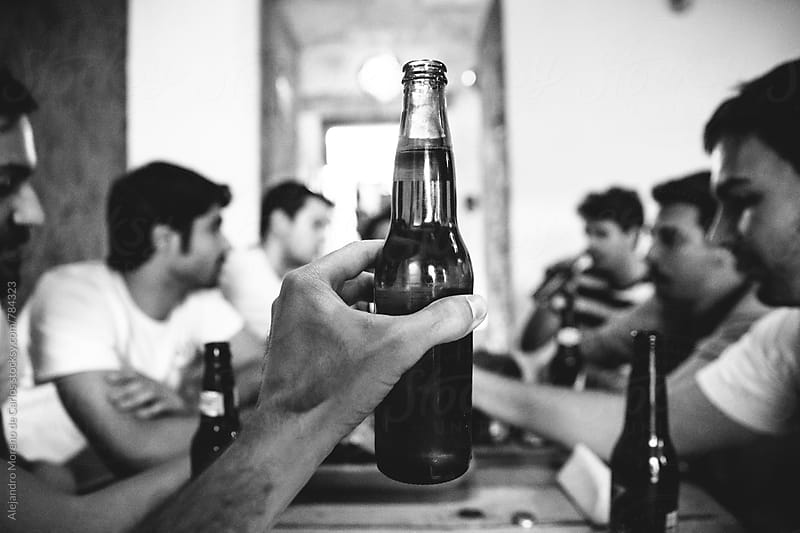 Man hand holding up a full beer bottle in front of a group of people sitting at a table by Alejandro Moreno de Carlos for Stocksy United
