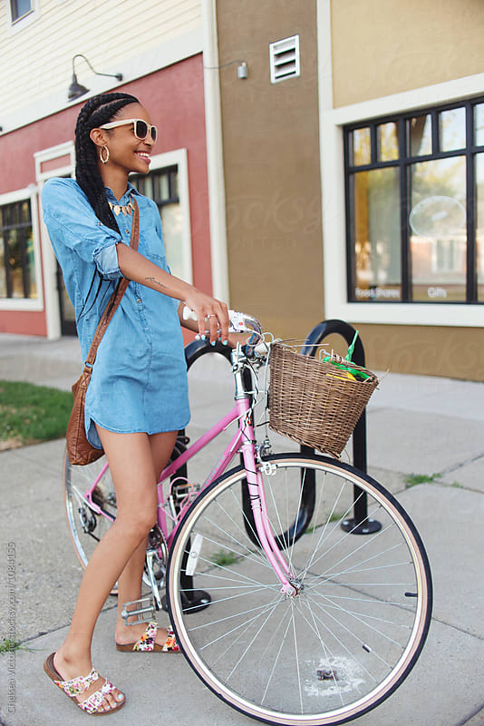 A young woman on a bike in the city by Chelsea Victoria for Stocksy United