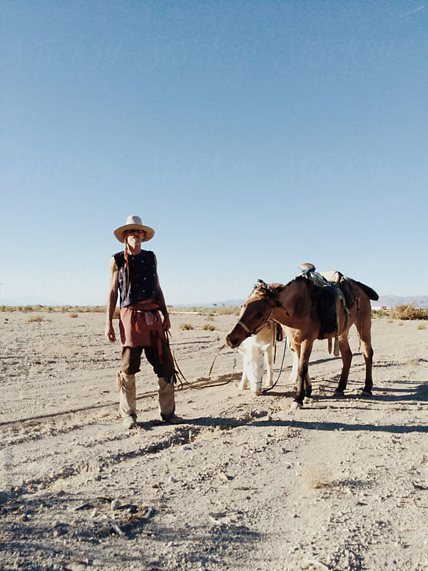 Man Holding Mules in the Desert by Kevin Russ for Stocksy United