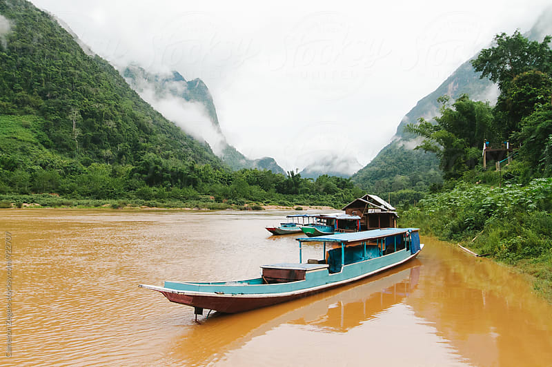 boats in Laos river by Cameron Zegers for Stocksy United