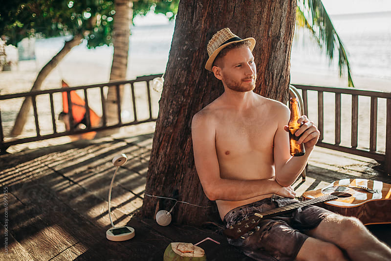Man Chilling at the Beach With a Bottle of Beer by Lumina for Stocksy United