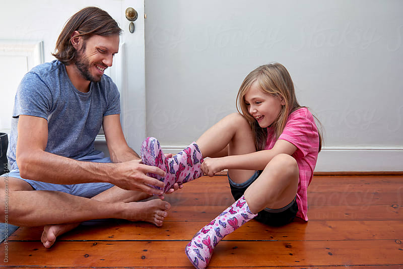 father helps daughter put on her shoes  by Daxiao Productions for Stocksy United