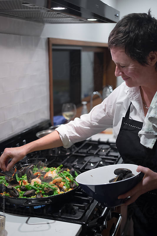 Cook finishing a dish of Spanish Paella by Rowena Naylor for Stocksy United