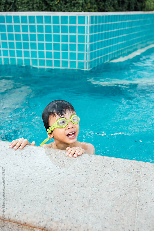 Young, cute, little swimmer looking at his Mother and waiting for instructions before swimming again by Lawrence del Mundo for Stocksy United
