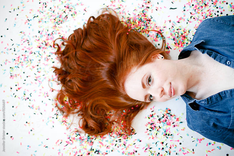 A woman lying on confetti by Jennifer Brister for Stocksy United