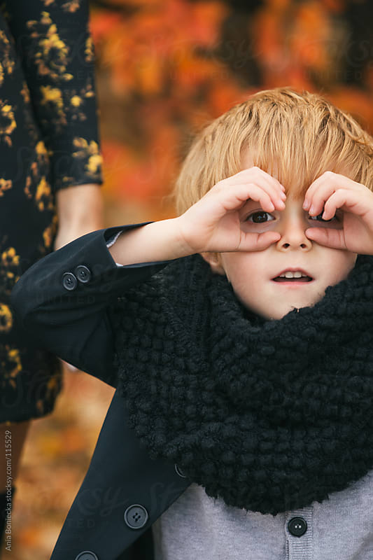 A blonde boy curiously looking through his hands shaped like binoculars  by Ania Boniecka for Stocksy United