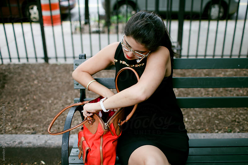 woman digs around in bag looking for something by Jennifer Brister for Stocksy United