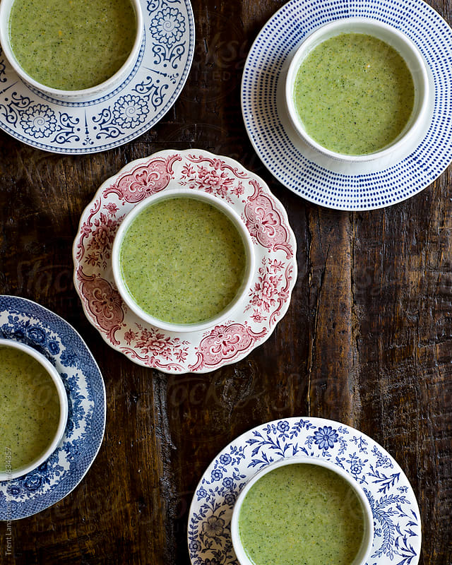 5 bowls on colored plates with green broccoli soup by Trent Lanz for Stocksy United