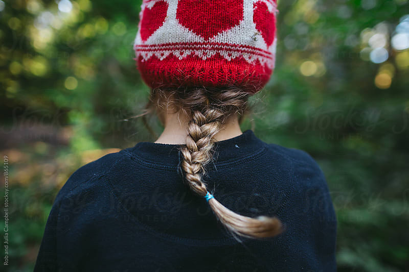 Back view of young girls braid and toque by Rob and Julia Campbell for Stocksy United