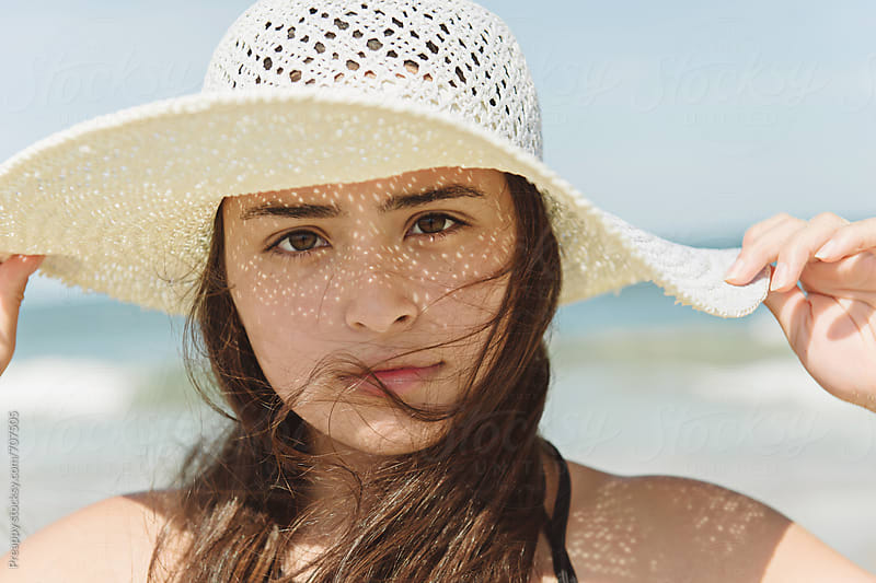 Teenage girl wearing sun hat at the beach by Preappy for Stocksy United