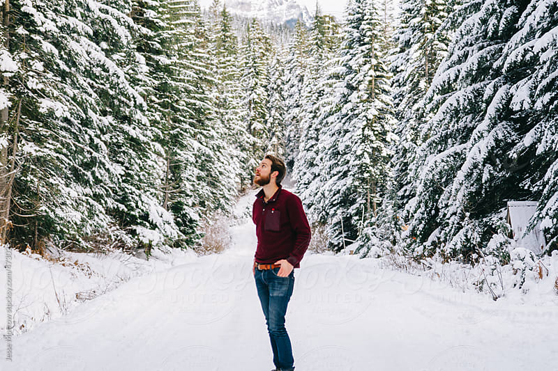 Young man standing on wintery road in middle of forest by Jesse Morrow for Stocksy United