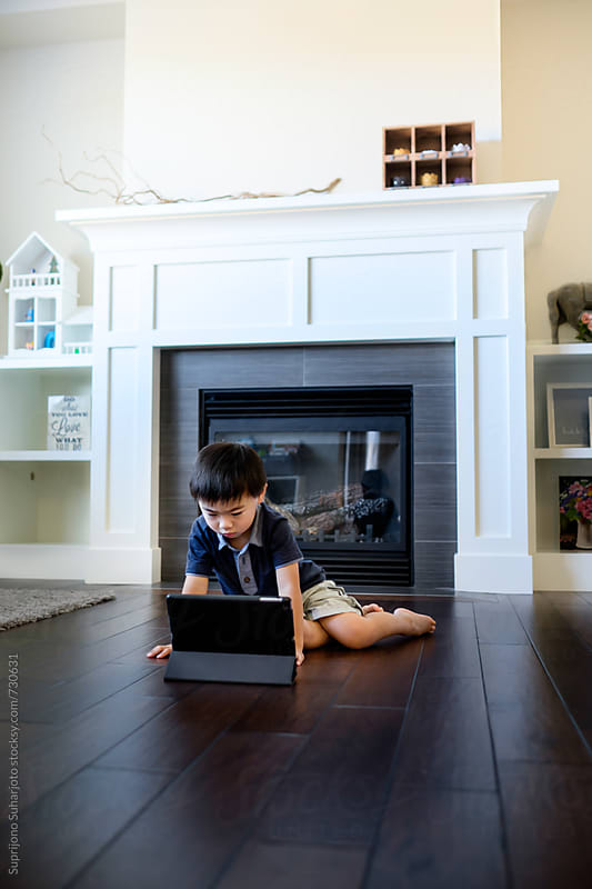 Asian boy watching on his tablet at home by Suprijono Suharjoto for Stocksy United