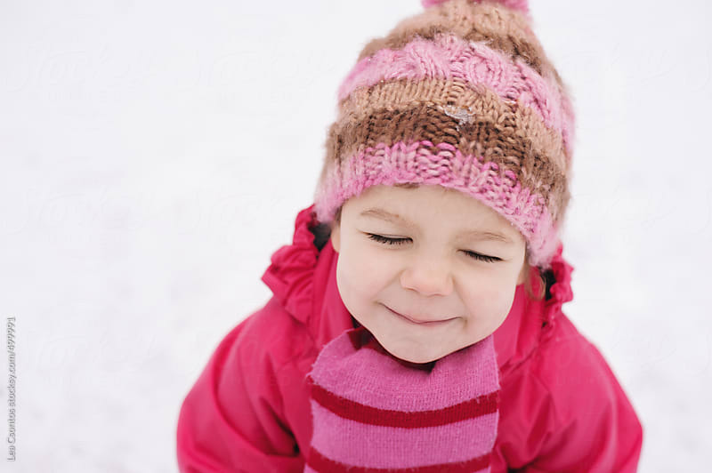 Little girl enjoying her time spent outdoors in snowy weather with her eyes closed. by Lea Csontos for Stocksy United