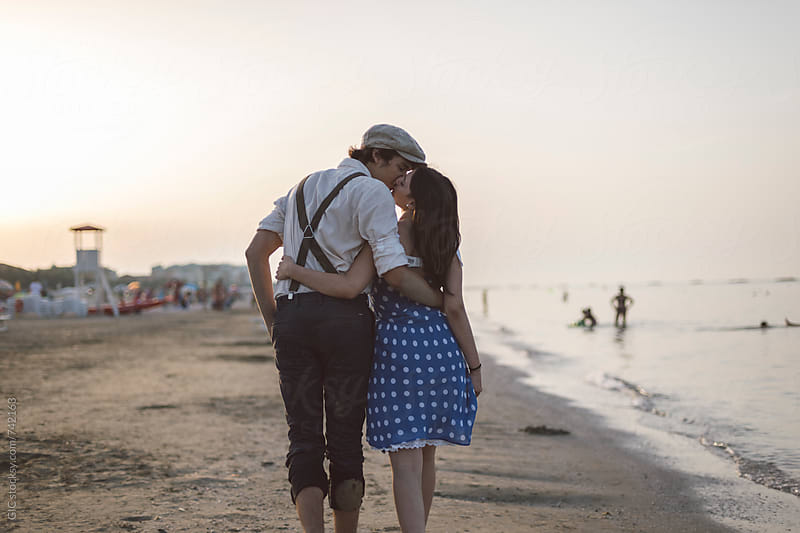 Young couple vintage dressed having fun on the beach by Simone Becchetti for Stocksy United