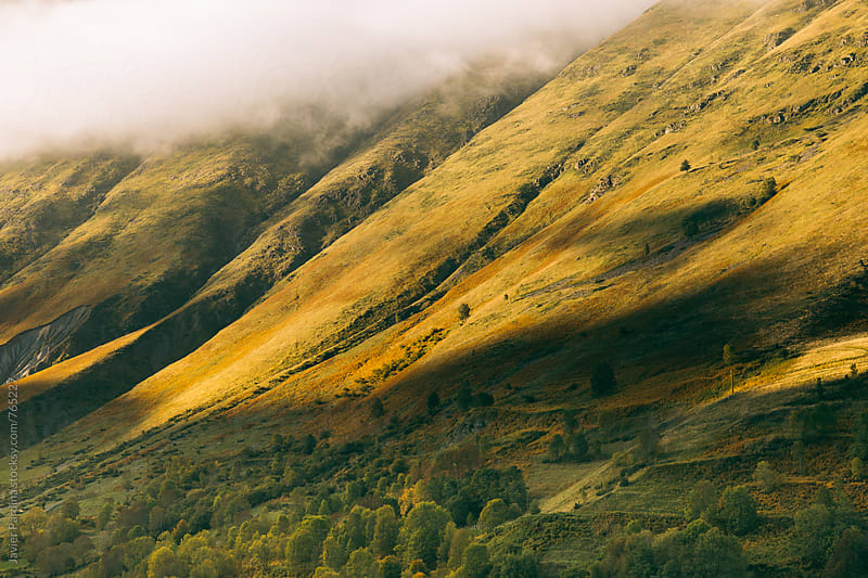 patr of mountains with clouds and shadow by Javier Pardina for Stocksy United