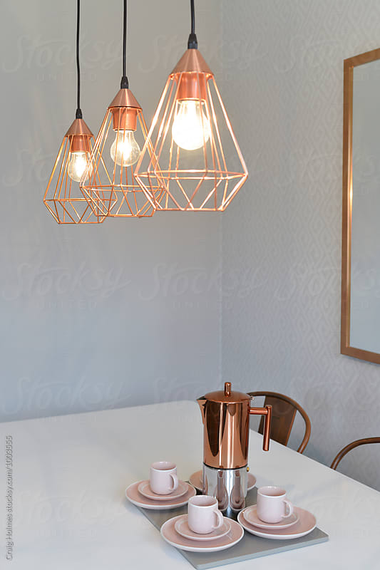 Rose gold colored espresso maker and lights on a table in a home. by Craig Holmes for Stocksy United