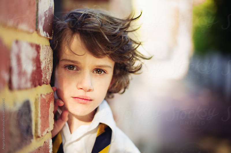 Boy looking out from behind a brick wall by Angela Lumsden for Stocksy United