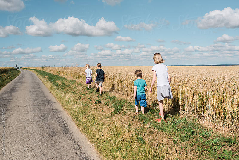 children on a walk in the summer by Léa Jones for Stocksy United