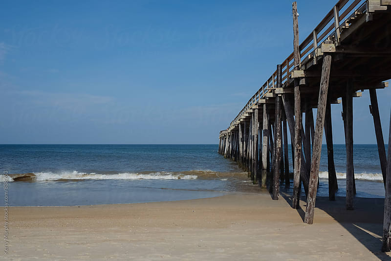 View of ocean and wooden fishing pier by Kerry Murphy for Stocksy United