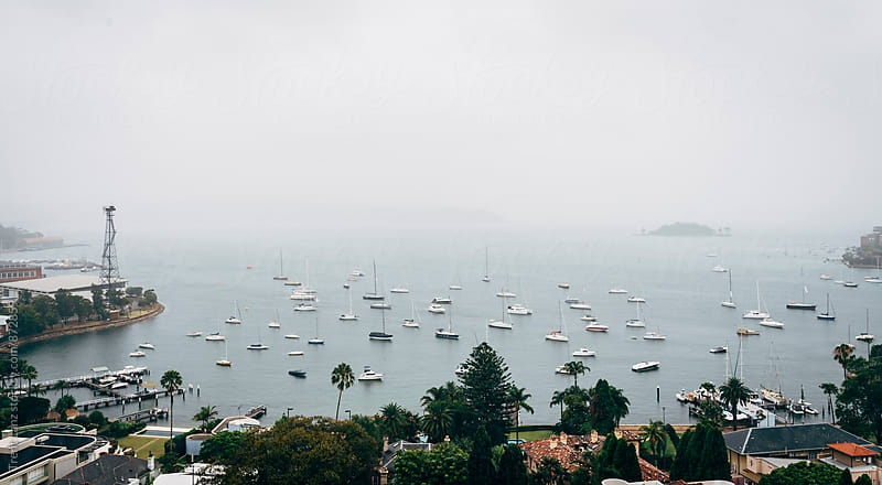 View on bay with sailing boats on a foggy morning by Trent Lanz for Stocksy United