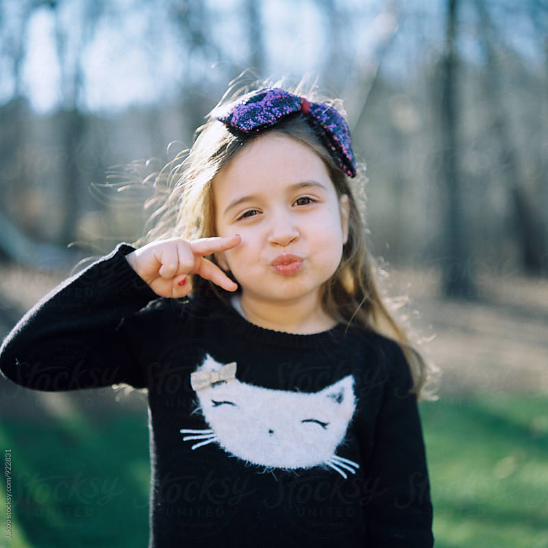 Cute young girl making a duck face and a sign with her hand by Jakob for Stocksy United