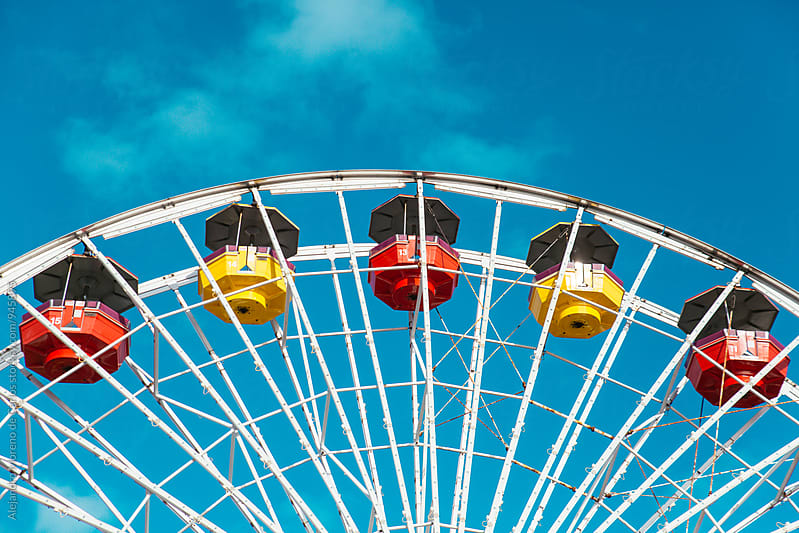Close- up of bright ferris wheel against of blue sky by Alejandro Moreno de Carlos for Stocksy United