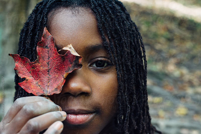 African American girl holding an autumn leaf in front of her eye by Gabriel (Gabi) Bucataru for Stocksy United