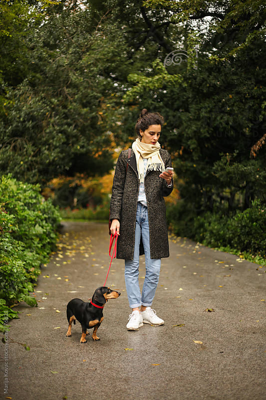 Stylish woman with a dog looking at the mobile phone  by Marija Kovac for Stocksy United