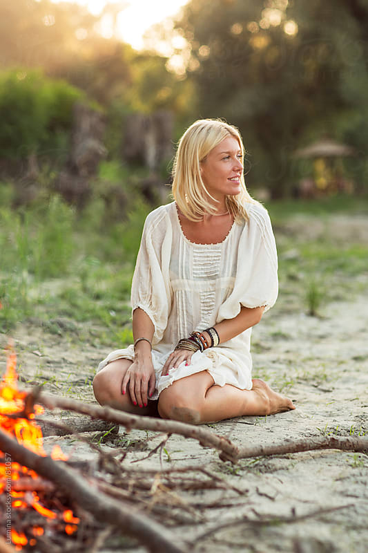 Woman Sitting by the Fire on the Beach by Lumina for Stocksy United