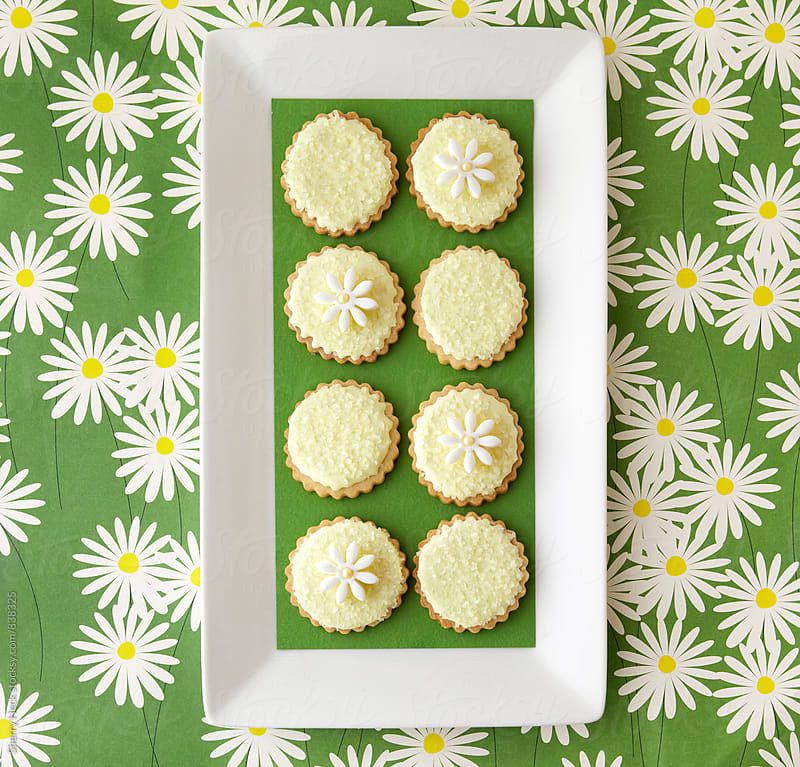 Iced sugar cookies on a rectangular plate on a surface with daisy-printed paper by Sherry Heck for Stocksy United