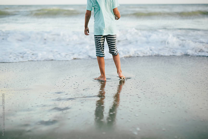boy standing at the edge of the ocean by Kelly Knox for Stocksy United