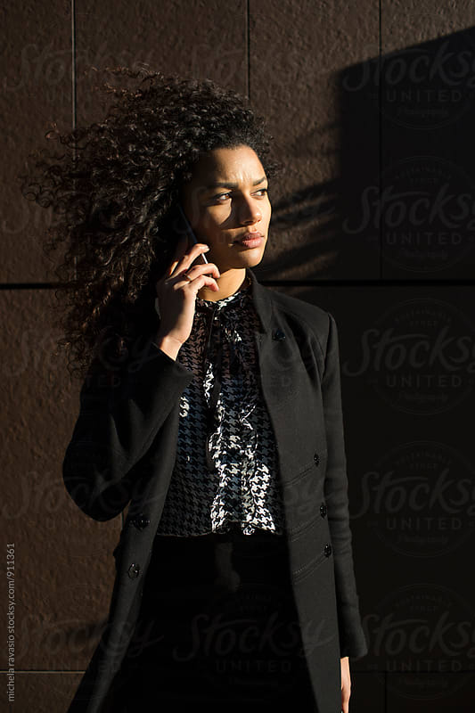 Charming businesswoman at work using her cell phone by michela ravasio for Stocksy United