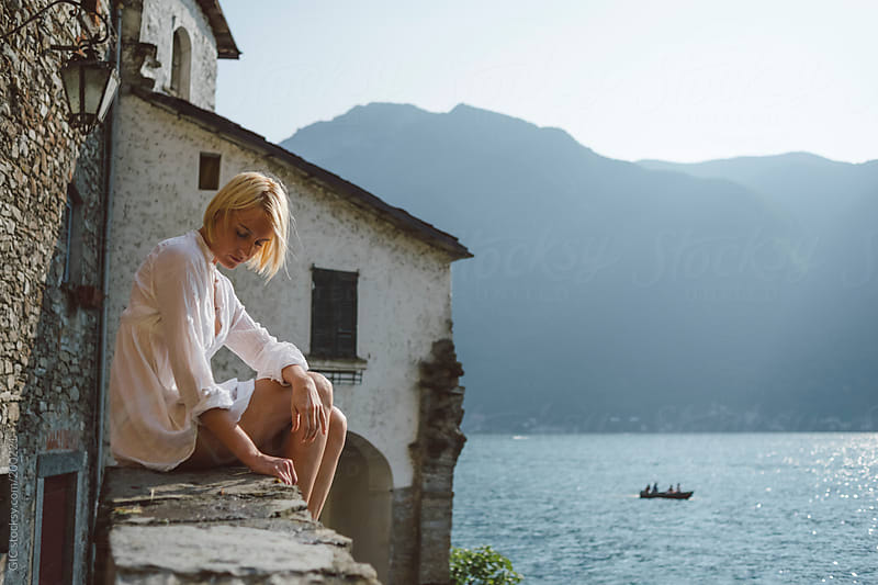 Young blonde woman sitting across the lake  by GIC for Stocksy United