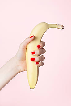 88a473744042de Banana In Female Hand On Pink Background