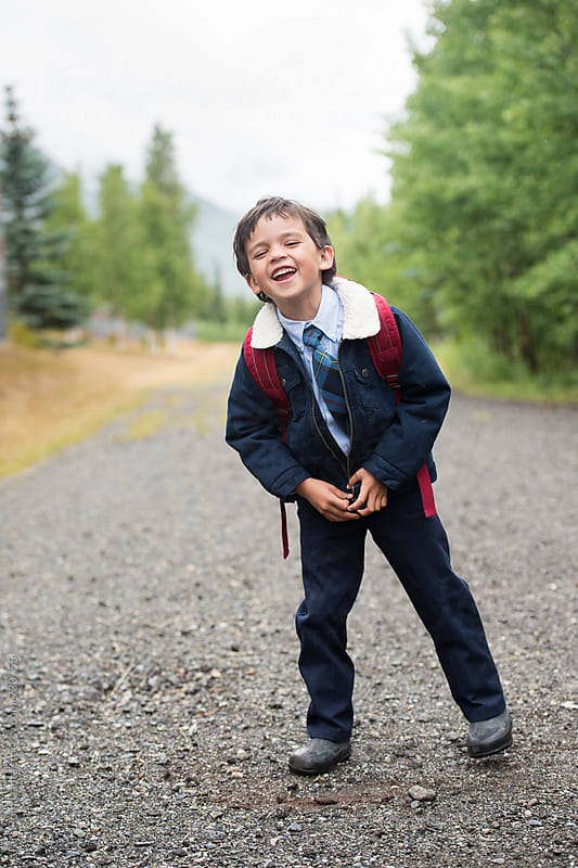 laughing school boy in uniform and with backpack by Tara Romasanta for Stocksy United
