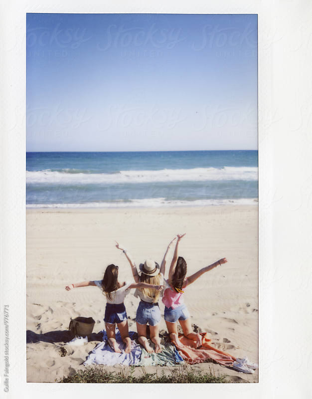Instant shot of three happy girlfriends with raised arms on beach by Guille Faingold for Stocksy United