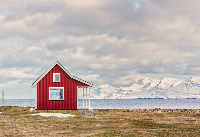 Traditional red Icelandic house by the sea and mountains in winter by Søren Egeberg Photography for Stocksy United