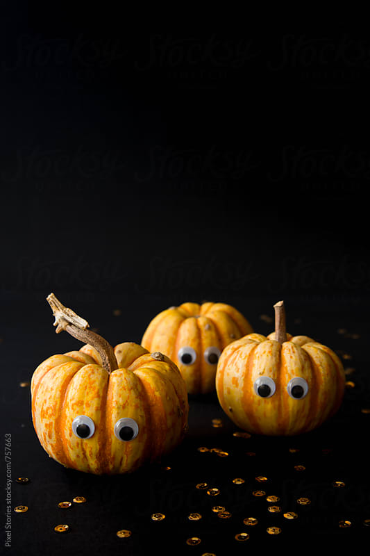 Three small pumpkins with googly eyes on black by Pixel Stories for Stocksy United