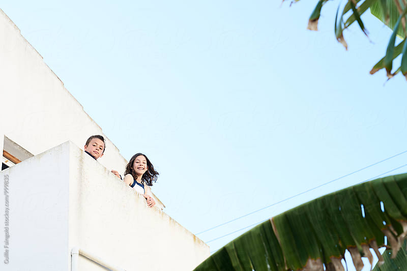 Two kids looking at camera from balcony by Guille Faingold for Stocksy United