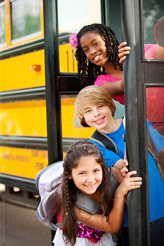 School Bus: Friends Peek Around Bus Door by Sean Locke for Stocksy United