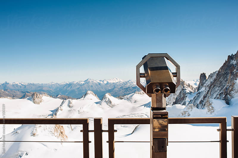 Viewing telescope looking out over mountains covered in snow by Suzi Marshall for Stocksy United