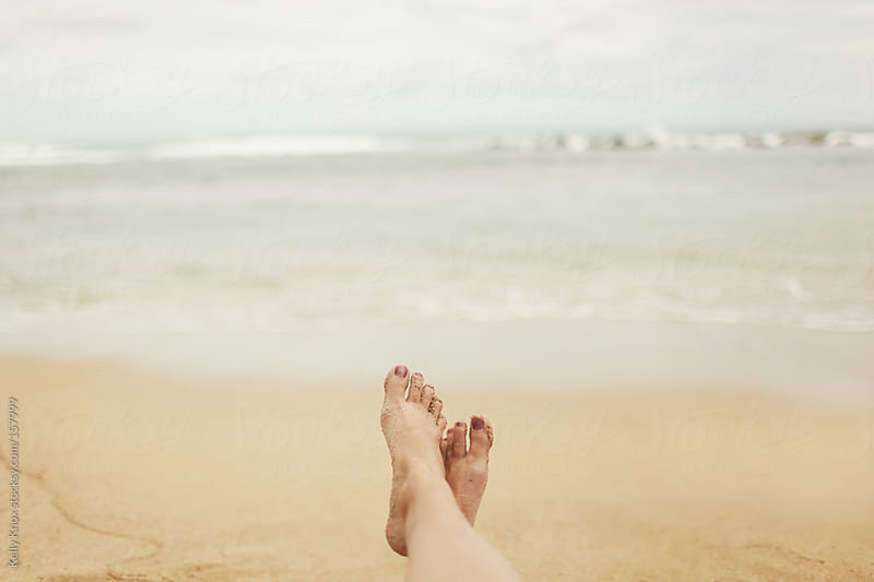 woman's feet crossed in front of the ocean by Kelly Knox for Stocksy United