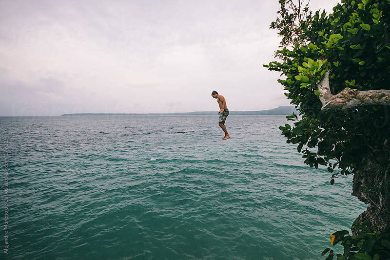 Young man jumping off a cliff into the sea by Alejandro Moreno de Carlos for Stocksy United